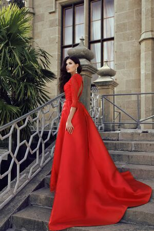lady in red: fashion outdoor photo of beautiful woman with dark hair wears luxurious dress,posing in summer park on villas stairs Stock Photo