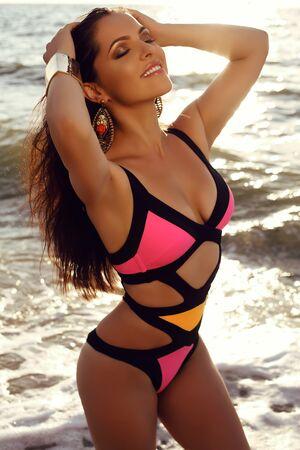 tanned girl: fashion outdoor photo of beautiful girl with dark hair in elegant bright bikini relaxing on summer beach