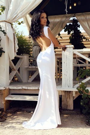 fashion outdoor photo of beautiful sensual woman with dark hair in elegant white dress with open back Stock Photo