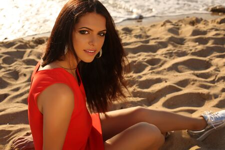 red hair girl: fashion outdoor photo of beautiful girl with dark hair in elegant red dress relaxing on summer beach