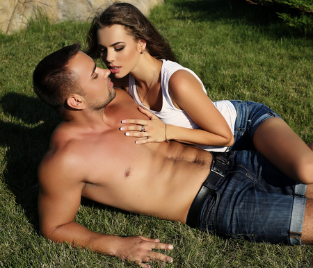 fashion outdoor photo of sensual impassioned couple.beautiful gorgeous woman and tanned handsome man embracing in summer garden