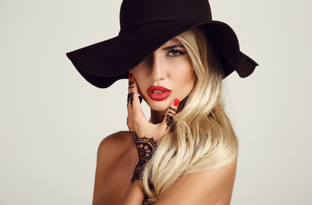 sensual: fashion studio portrait of beautiful sensual woman with blond hair with evening makeup and henna tattoo on hands