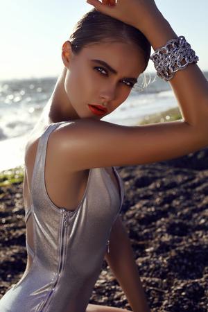 petite fille maillot de bain: mode photo en plein air de belle fille sensuelle avec des cheveux blonds porte maillot de bain d'argent de luxe avec des accessoires posant à côté d'un lac Banque d'images