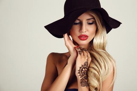 rubia: estudio de la moda retrato de la hermosa mujer sensual con el pelo rubio con maquillaje de noche y tatuaje de henna en las manos Foto de archivo