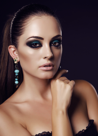 makeup eyes: fashion studio portrait of beautiful sexy girl with dark hair and evening makeup with bijou Stock Photo