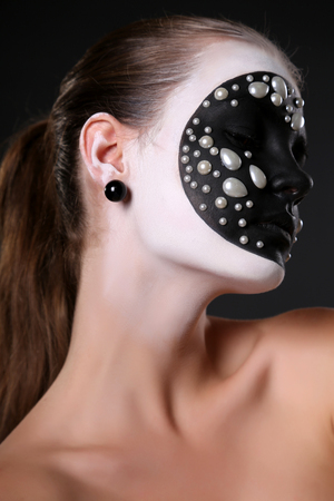 halloween pattern: fashion studio portrait of young girl with black and white art pattern on her face.Halloween style