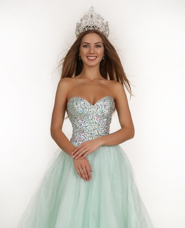 contest: fashion studio photo of beautiful smiling woman with long hair wears luxurious sequin dress and precious crown. winner of beauty contest