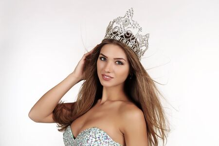 beauty contest: fashion studio photo of beautiful smiling woman with long hair wears luxurious sequin dress and precious crown. winner of beauty contest