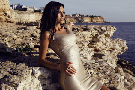 fashion outdoor photo of beautiful gorgeous woman with long dark hair wears elegant gold dress with accessories,posing on sea coast