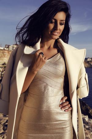 mujer elegante: moda foto al aire libre de la hermosa mujer hermosa con el pelo largo y oscuro viste el vestido de oro elegante y abrigo de lana con accesorios, posando en la costa del mar