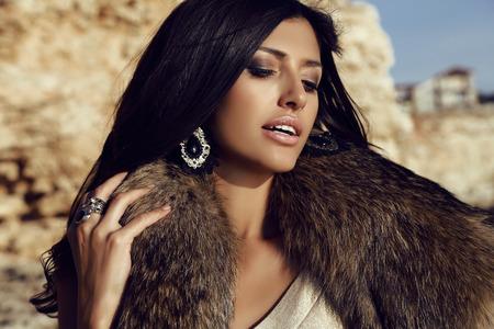 de fotografía de moda al aire libre de la hermosa mujer hermosa, con el pelo oscuro largo viste de piel y accesorios, presenta en costa de mar