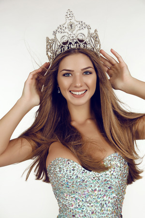 fashion studio photo of beautiful smiling woman with long hair wears luxurious sequin dress and precious crown. winner of beauty contest
