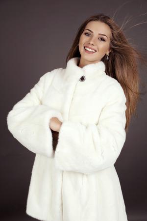 bata blanca: estudio de moda foto de la mujer sonriente hermosa con el pelo largo lleva abrigo de piel blanca de lujo Foto de archivo