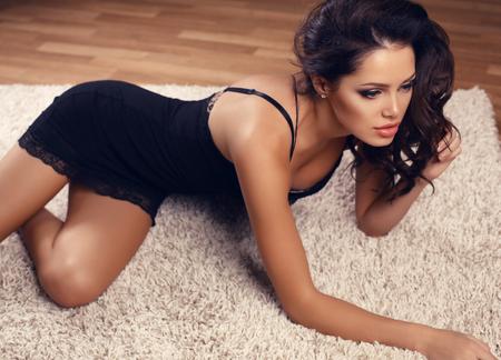 moda foto interior de mujer sexy hermosa con el pelo oscuro en lencería de encaje, mentir sobre la alfombra de color beige
