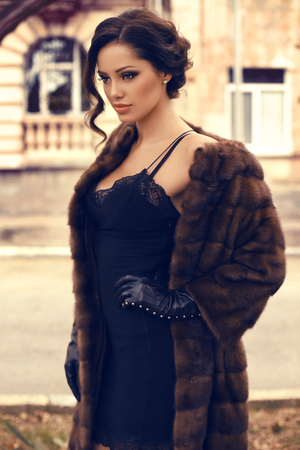 leather: fashion outdoor photo of beautiful sensual woman with dark hair wearing luxurious fur coat and leather gloves,posing at autumn park