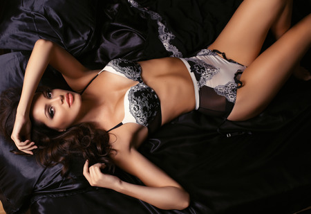 fashion interior photo of beautiful sexy woman with dark hair in elegant lace lingerie lying on bed in bedroom
