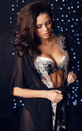fashion interieur foto van mooie sensuele brunette in elegante kant lingerie en robe