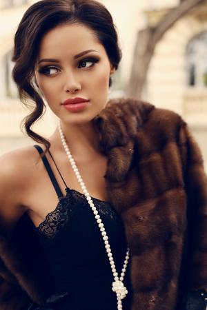 秋の公園でポーズ豪華な毛皮のコートを着ている黒髪の美しい官能的な女性のファッション屋外写真