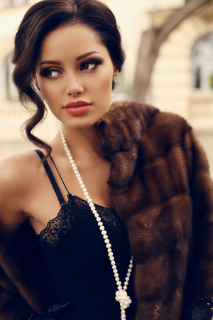 fashion outdoor photo of beautiful sensual woman with dark hair wearing luxurious fur coat posing at autumn park