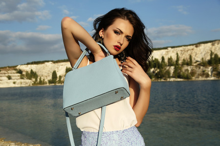 fashion outdoor photo of gorgeous young woman with short dark hair wears elegant dress,posing on summer beach,holding bag in hands