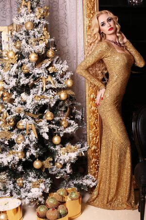 sexy dress: fashion interior photo of beautiful gorgeous woman with blond hair in luxurious dress posing in room with Christmas tree and decorations Stock Photo