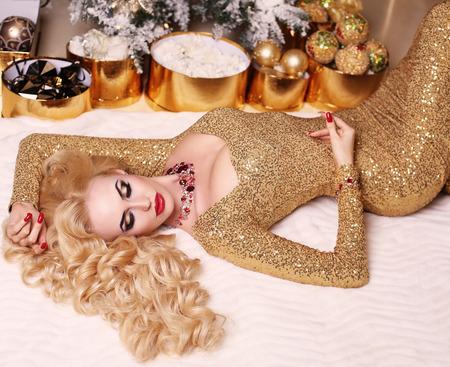 mujer con rosas: moda foto interior de la hermosa mujer hermosa con el pelo rubio en el lujoso vestido posando en la habitación con el árbol de Navidad y adornos