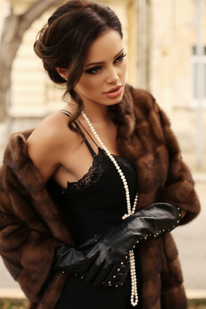 fur: fashion outdoor photo of beautiful sensual woman with dark hair wears luxurious fur coat,posing in autumn park