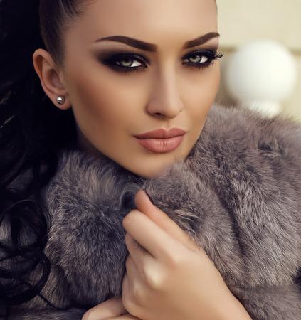americana: moda foto al aire libre de la hermosa mujer con el pelo largo y oscuro lleva abrigo de piel de lujo, que presenta en parque del otoño