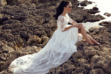 gorgeous: fashion outdoor photo of gorgeous young woman with long dark hair in luxurious lace wedding dress,dreaming on the sea coast Stock Photo