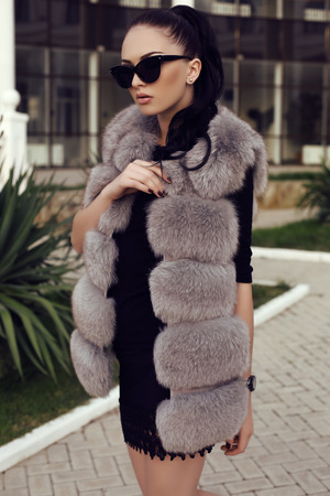 fur: fashion outdoor photo of gorgeous woman with long dark hair wears luxurious fur coat and sunglasses, walking by the street Stock Photo