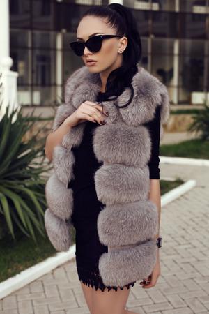 manteau de fourrure: mode photo en plein air de la magnifique femme avec de longs cheveux noirs porte manteau et des lunettes de soleil de fourrure de luxe, en marchant par la rue Banque d'images