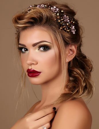 fashion studio portrait of beautiful young woman with dark hair with bright makeup and luxurious headband