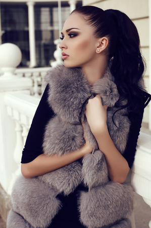 fashion outdoor photo of gorgeous woman with long dark hair wears luxurious fur coat, posing in autumn park