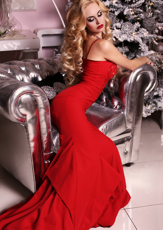 sexy girl posing: fashion interior photo of beautiful gorgeous woman with blond hair in luxurious dress posing in room with Christmas tree and decorations Stock Photo