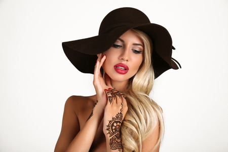 black hat: fashion studio portrait of beautiful sensual woman with blond hair in elegant black hat with henna tattoo on hands