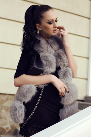 fur: fashion outdoor photo of gorgeous woman with long dark hair wears luxurious fur coat,posing on stairs