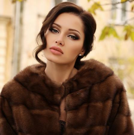 sexy dress: fashion outdoor photo of beautiful sensual woman with dark hair wears luxurious fur coat,posing in autumn park