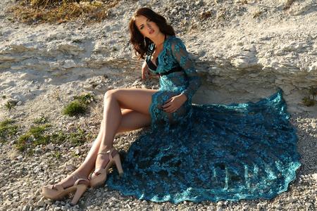 belle brune: mode photo en plein air de la magnifique jeune femme avec les cheveux foncés courts porte la robe de dentelle de luxe, posant sur la plage d'été