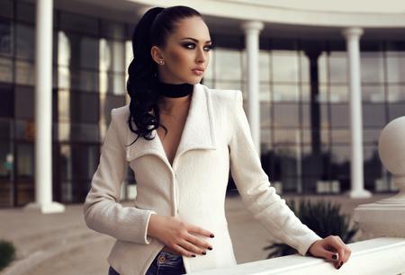 mujeres morenas: moda foto al aire libre de la hermosa mujer con el pelo largo y oscuro viste ropa elegante, que presenta en parque del otoño