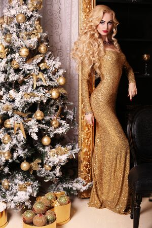 rubia: moda foto interior de la hermosa mujer hermosa con el pelo rubio en el lujoso vestido posando en la habitaci�n con el �rbol de Navidad y adornos