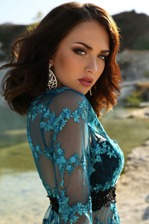 short: fashion outdoor photo of gorgeous young woman with short dark hair wears luxurious lace robe,posing on summer beach