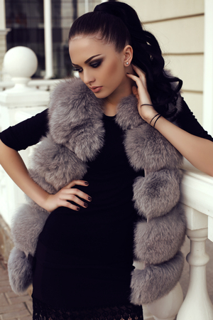 gorgeous girl: fashion outdoor photo of gorgeous woman with long dark hair wears luxurious fur coat, posing on the street Stock Photo