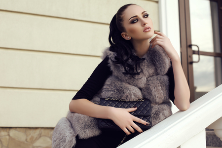 fashion outdoor photo of gorgeous woman with long dark hair wears luxurious fur coat, posing on stairs