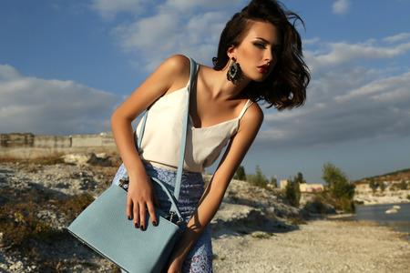 mode: fashion outdoor foto van prachtige jonge vrouw met kort donker haar draagt elegante jurk, die zich voordeed op zomer strand, met tas in handen Stockfoto