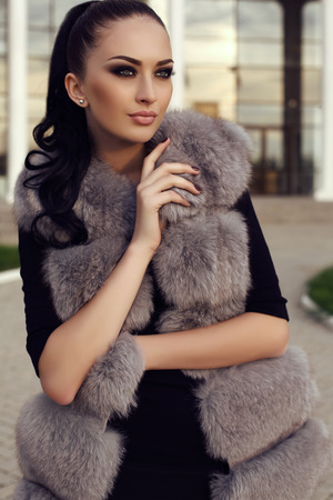 gorgeous woman: fashion outdoor photo of gorgeous woman with long dark hair wears luxurious fur coat, posing on street