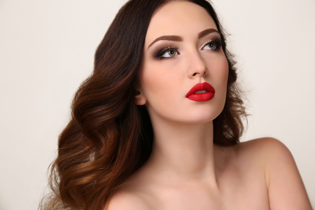 brows: fashion studio portrait of beautiful young woman with luxurious dark hair and evening makeup