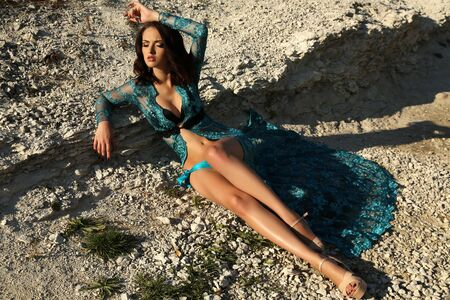 sensual girl: fashion outdoor photo of gorgeous young woman with short dark hair wears luxurious lace robe,posing on summer beach
