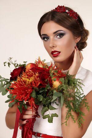 labios sexy: estudio de la moda retrato de mujer joven y hermosa con el pelo oscuro con maquillaje brillante y diadema de lujo, con ramo de flores