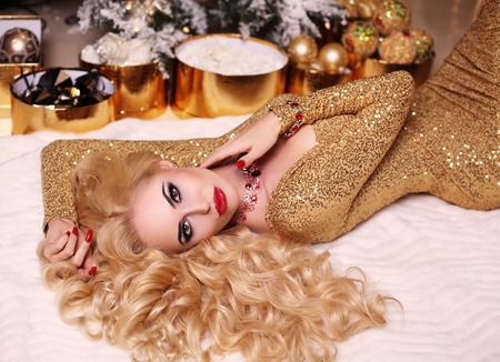 fashion interior photo of beautiful gorgeous woman with blond hair in luxurious dress posing in room with Christmas tree and decorations 스톡 콘텐츠