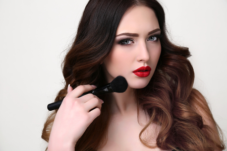 sexy female: fashion studio portrait of beautiful young woman with luxurious dark hair and evening makeup,holding powder brush in hand